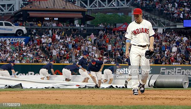 Grady Sizemore of the Cleveland Indians leves the field as the grounds crew unrolls the tarp during the seventh inning against the Pittsburgh Pirates...