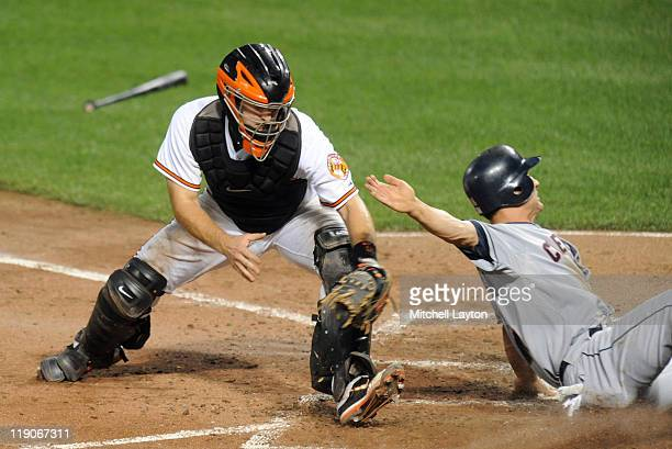 Grady Sizemore of the Cleveland Indians slides into home plate past Craig Tatum of the Baltimore Orioles during the sixth inning of a baseball game...