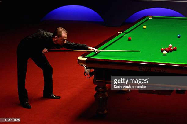 Graeme Dott of Scotland plays a shot in the round two game against Ali Carter of England on day seven of the Betfredcom World Snooker Championship at...