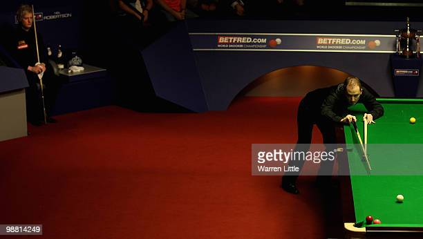 Graeme Dott of Scotland plays as Neil Robertson of Australia looks on during the final of the Betfredcom World Snooker Championships at The Crucible...