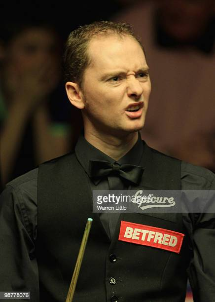Graeme Dott of Scotland reacts to a poor shot against Mark Selby of England during the semi final of the Betfredcom World Snooker Championships at...