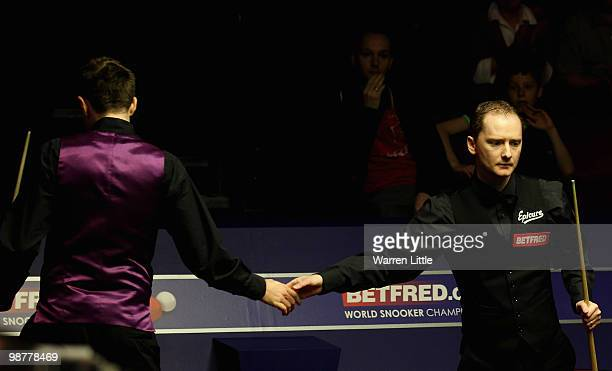 Graeme Dott of Scotland shakes hands with Mark Selby of England after taking a four frame lead in the morning session during the semi final of the...