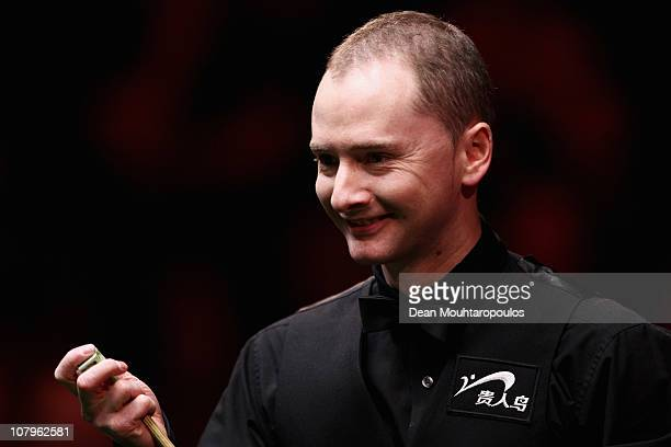 Graeme Dott of Scotland smiles as he chalks his cue in his Round One match against John Higgins of Scotland during The Ladbrokesmobile Masters on Day...