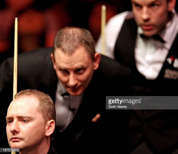 Graeme Dott referee Brendan Moore and Allister Carter line up a shot during day four of The Masters at Alexandra Palace on January 18 2012 in London...
