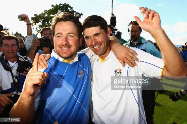 Graeme McDowell of Europe celebrates his 3&1 win to secure victory for the European team on the 17th green with Padraig Harrington in the singles...