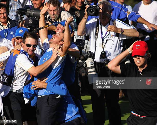 Graeme McDowell of Europe celebrates with his team mates and caddies after his 31 win to secure victory for the European team on the 17th green in...