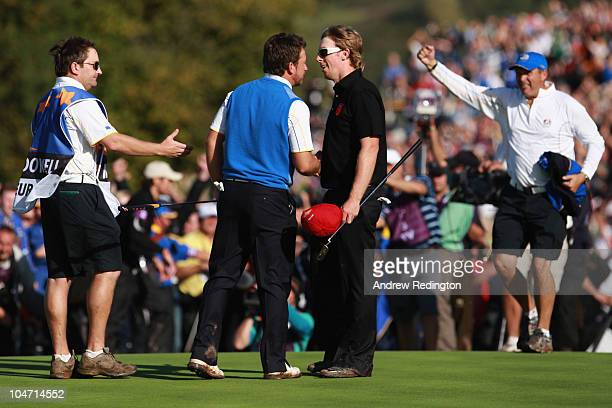 Graeme McDowell of Europe shakes hands with Hunter Mahan of the USA after securing victory for the European team on the 17th green in the singles...