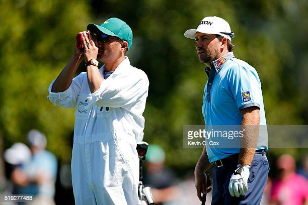 Graeme McDowell of Northern Ireland and his caddie Ken Comboy check the distance of a shot during a practice round prior to the start of the 2016...