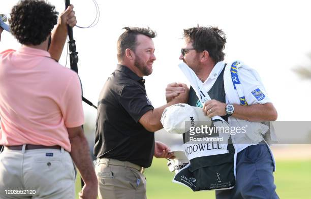 Graeme McDowell of Northern Ireland celebrates with his caddie during Day 4 of the Saudi International at Royal Greens Golf and Country Club on...