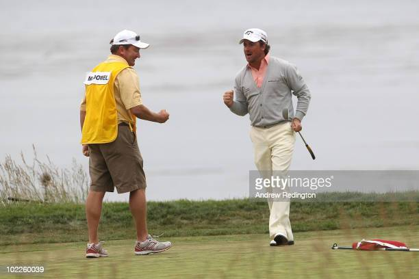 Graeme McDowell of Northern Ireland celebrates with his caddie Ken Comboy after making par on the 18th hole to win the 110th U.S. Open at Pebble...