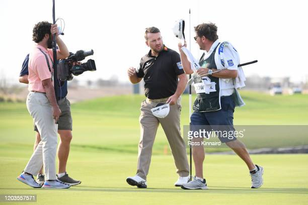 Graeme McDowell of Northern Ireland celebrates with his caddie on the 18th green during Day 4 of the Saudi International at Royal Greens Golf and...