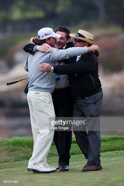 Graeme McDowell of Northern Ireland celebrates with his father Ken and agent Connor Ridge on the 18th green after winning thethe 110th US Open at...