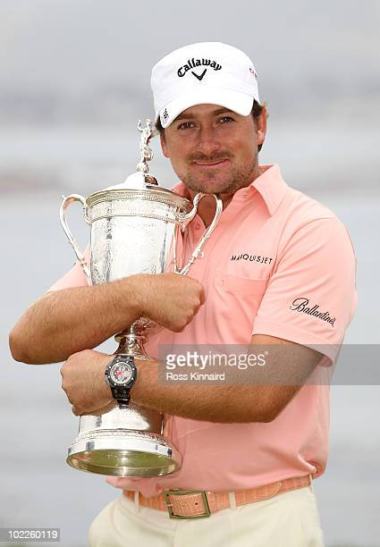 Graeme McDowell of Northern Ireland celebrates with the trophy on the 18th green after winning the 110th U.S. Open at Pebble Beach Golf Links on June...