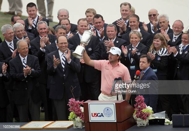 Graeme McDowell of Northern Ireland celebrates with the trophy on the 18th green as Bob Costas of NBC Sports looks on after winning the 110th US Open...