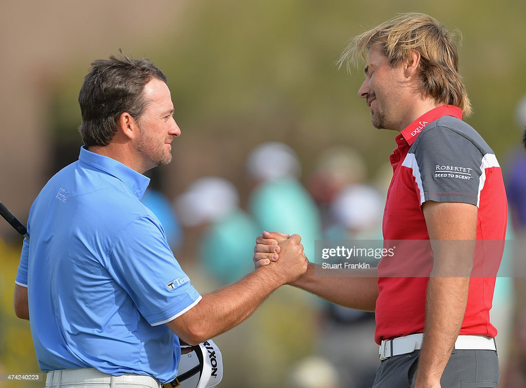 Graeme McDowell of Northern Ireland congratulates Victor Dubuisson of France on the 18th hole during the quarterfinal round of the World Golf Championships - Accenture Match Play Championship at The Golf Club at Dove Mountain on February 22, 2014 in Marana, Arizona.