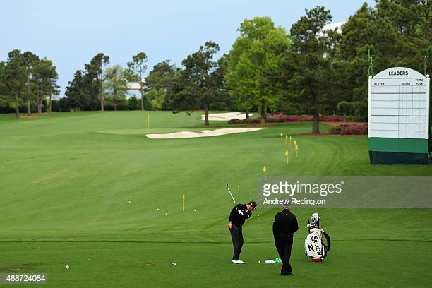 Graeme McDowell of Northern Ireland hits as his coach Pete Cowen looks on during a practice round prior to the start of the 2015 Masters Tournament...