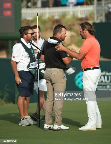 Graeme McDowell of Northern Ireland is congratulated by Victor Dubiosson of France on the 18th green during Day 4 of the Saudi International at Royal...