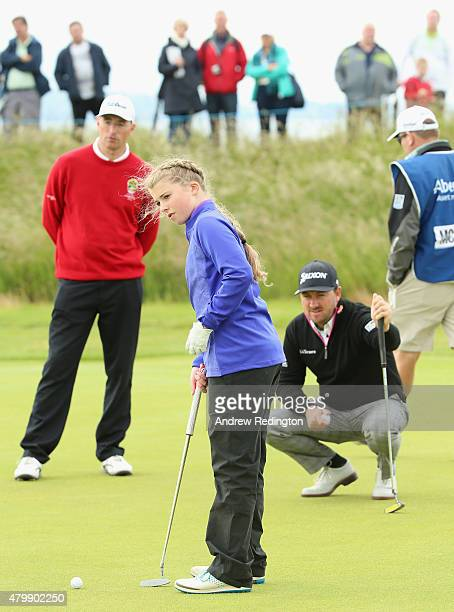Graeme McDowell of Northern Ireland lines up a putt on the second green with Anna McKay of the ClubGolf initiative as her caddie looks on during the...