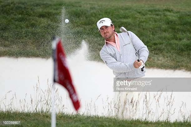 Graeme McDowell of Northern Ireland plays a bunker shot on the 12th hole during the final round of the 110th US Open at Pebble Beach Golf Links on...