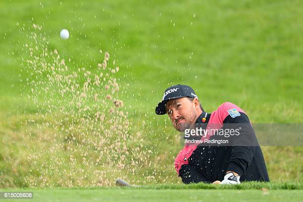 Graeme McDowell of Northern Ireland plays his second shot from a bunker on the first hole during the fourth round of the British Masters at The Grove...