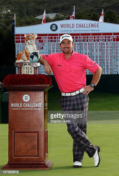 Graeme McDowell of Northern Ireland poses with the trophy after his three stroke victory in the final round of the Tiger Woods World Challenge...