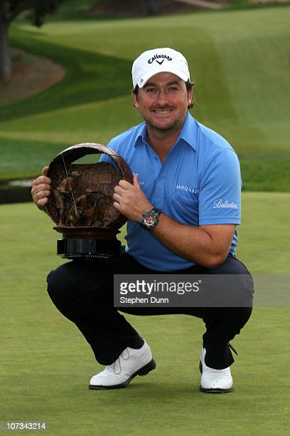 Graeme McDowell of Northern Ireland poses with the trophy after defeating Tiger Woods on the first playoff hole in the final round of the Chevron...