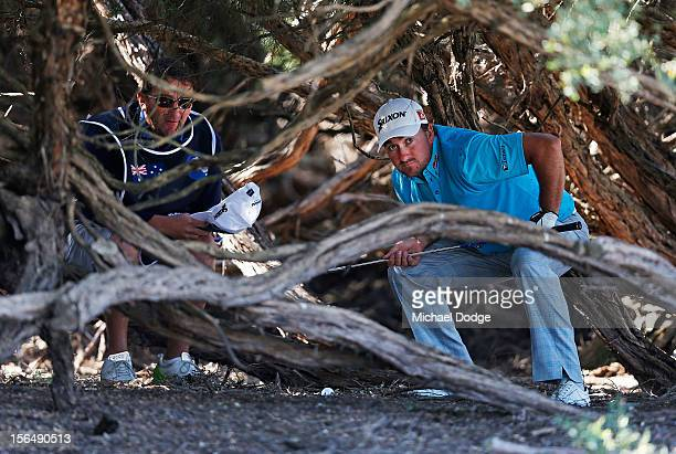 Graeme McDowell of Northern Ireland prepares to play a shot out from the trees on the 16th hole during day two of the Australia Masters at Kingston...