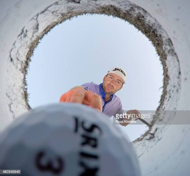 Graeme McDowell of Northern Ireland takes a ball out of a golf hole on the putting green during a practice round prior to the Omega Dubai Desert...