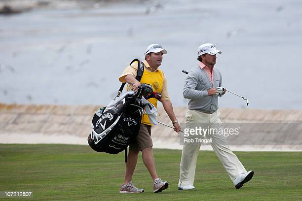 Graeme McDowell of Northern Ireland walks down the 18th fairway with his caddie Ken Comboy during the final round of the 110th US Open at Pebble...