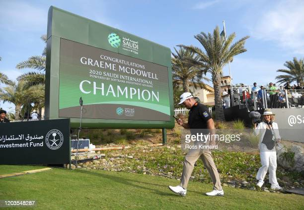 Graeme McDowell of Northern Ireland walks past a big screen congratulating him following Day 4 of the Saudi International at Royal Greens Golf and...