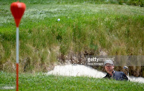 Graeme McDowell of Northern Ireland watches his third shot from a greenside bunker on the 17th hole during Round Two of the 113th U.S. Open at Merion...