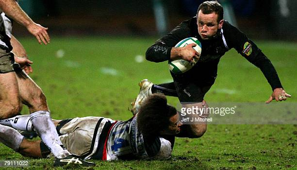 Graeme Morrison of Glasgow Warriors is tackled by Richard Haughton of Saracens during the Heineken Cup match at Firhill Stadium January 18 2008 in...