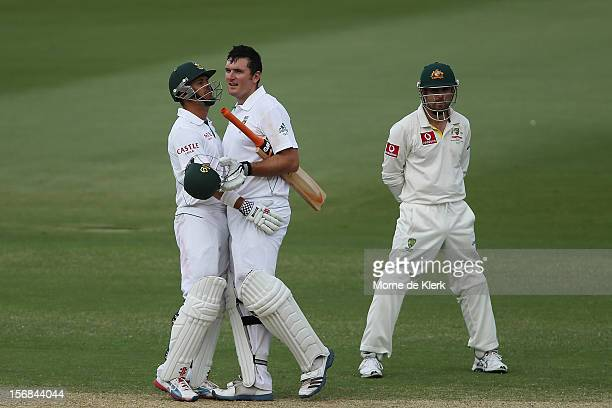 Graeme Smith of South Africa celebrates after reaching 100 runs with his teammate Jacques Rudolph as Ed Cowan of Australia looks onduring day two of...