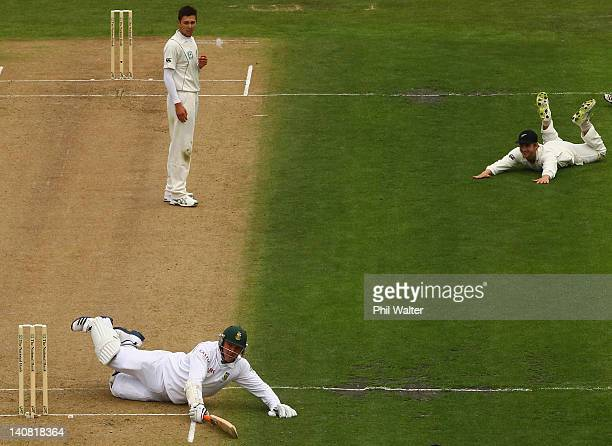Graeme Smith of South Africa makes his ground after a throw in from Kane Williamson of New Zealand as Trent Boult looks on during day one of the...