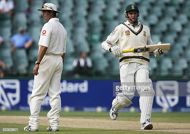 Graeme Smith of South Africa scores more runs as Michael Vaughan of England looks on during day five of the fourth test match between South Africa...