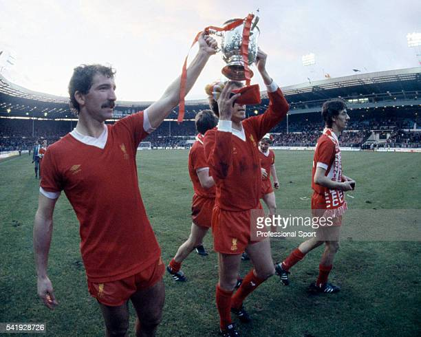 Graeme Souness and Phil Neal of Liverpool holding the League Cup following their victory over Tottenham Hotspur in the League Cup Final sponsored by...