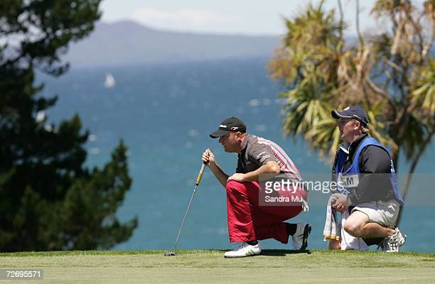 Graeme Storm of England and his caddy Dominic Bott of England line up a putt with Rangitoto Island in the background on the 16th hole during round...