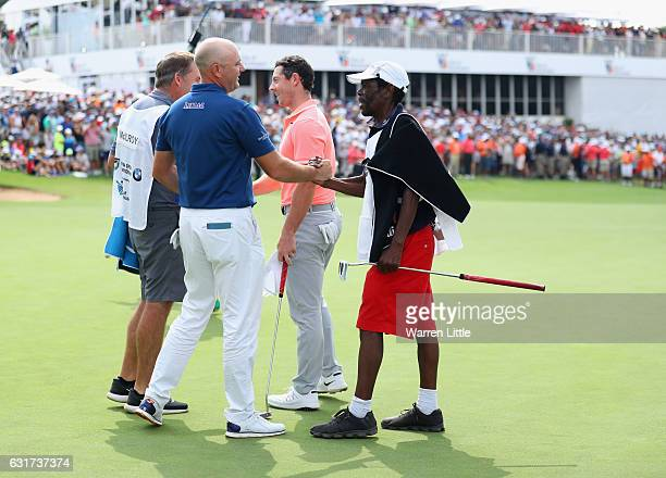 Graeme Storm of England is congratulated by his caddie Jeffrey Wkonyane on the 18th green after beating Rory McIlroy of Northern Ireland in the third...