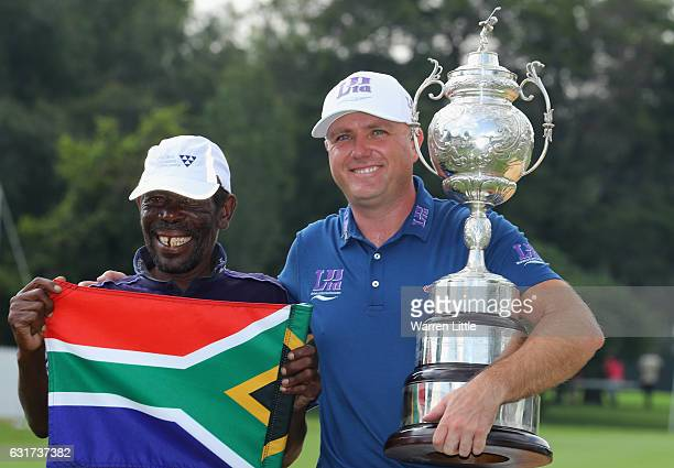 Graeme Storm of England poses with his caddie Jeffrey Wkonyane on the 18th green after beating Rory McIlroy of Northern Ireland in the third play off...