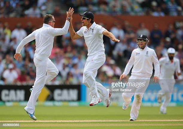 Graeme Swann of England celebrates with captain Alastair Cook after dismissing Chris Rogers of Australia during day one of the Second Ashes Test...