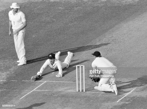 Graeme Wood of Australia slides in to make his ground as England wicketkeeper David Bairstow attempts to run him out during the Centenary Test match...