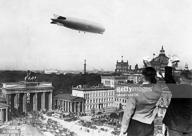 Graf Zeppelin over the Brandenburg Gate in Berlin the Victory Column and the Reichstag to the right in the right foreground two employees on the roof...