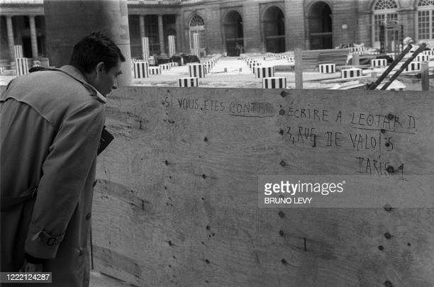 Graffiti against the work of French artist Daniel Buren is seen on the fence surrounding the site where columns are being erected in the Palais Royal...