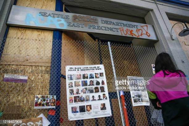Graffiti and photos of people killed by police are pictured on a fence outside the closed Seattle Police Department's East Precinct now surrounded by...