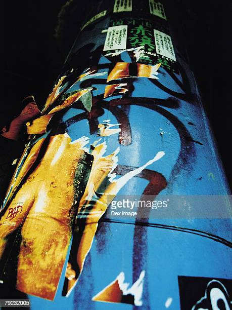 Graffiti and torn posters on lamp post