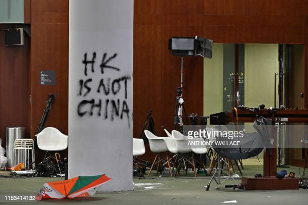 TOPSHOT Graffiti and umbrellas are seen outside the main chamber of the Legislative Council during a media tour in Hong Kong on July 3 two days after...