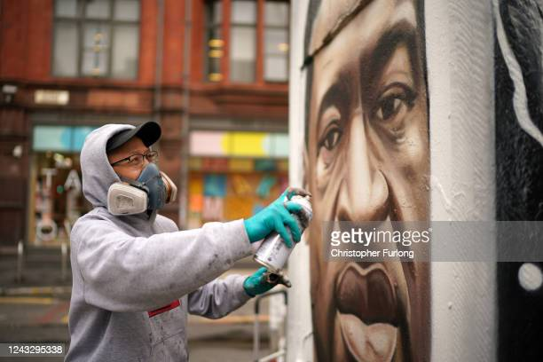 Graffiti artist Akse spray paints a mural of George Floyd in Manchester's northern quarter on June 03, 2020 in Manchester, United Kingdom. The death...