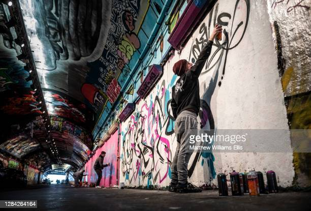 Graffiti artist at Waterloo Leake Street Graffiti Tunnels in central London, England, United Kingdom.