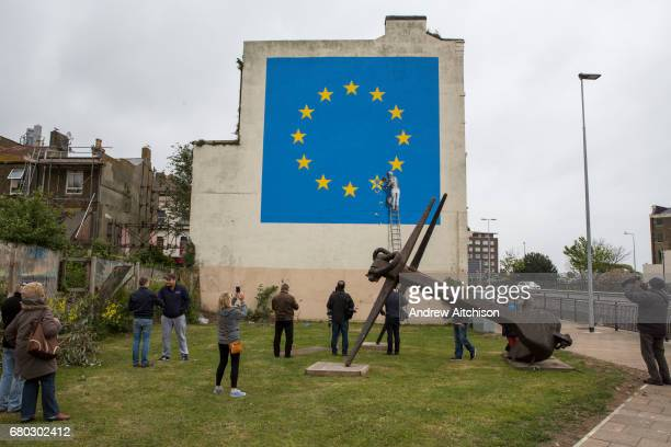 Graffiti artist Banksy has unveiled his latest piece about Brexit in Dover United Kingdom The artwork shows a man up a ladder chipping a gold star...