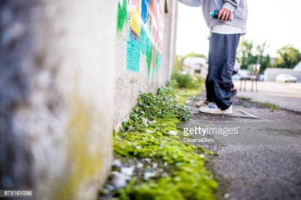 graffiti artist drawing graffiti on wall - baggy pants stock photos and pictures